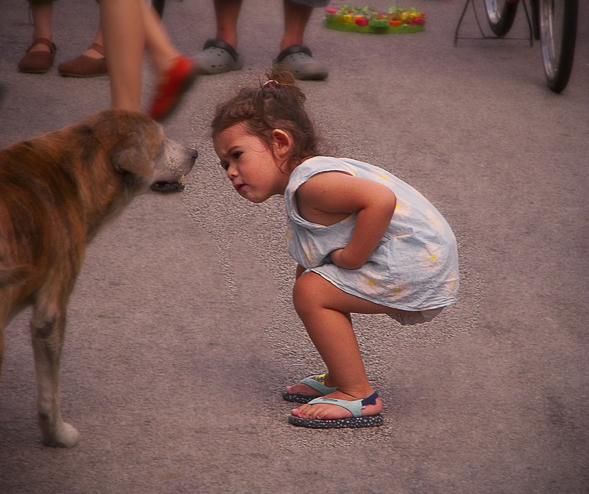 Young girls bent over looking at dog's health